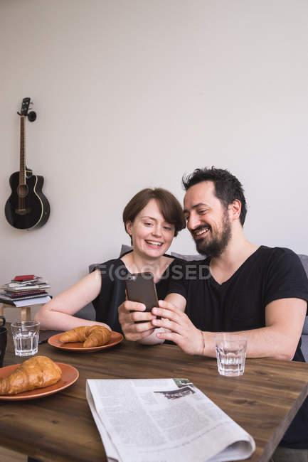 A young couple is doing selfies with a smart phone at the breakfast table. — Stock Photo