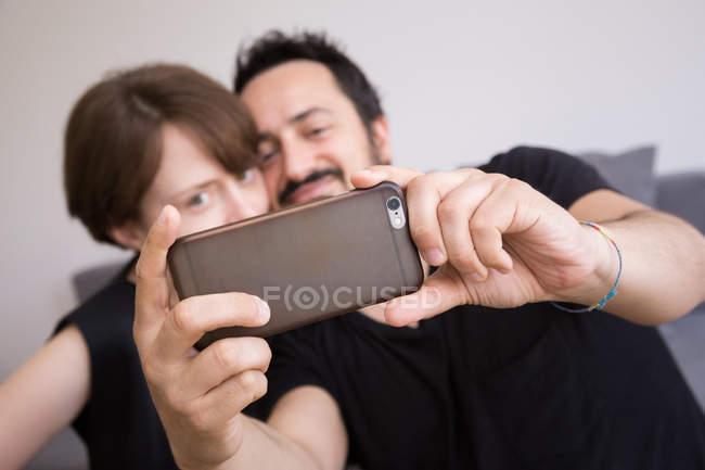 Um jovem casal está fazendo selfies com um telefone inteligente — Fotografia de Stock