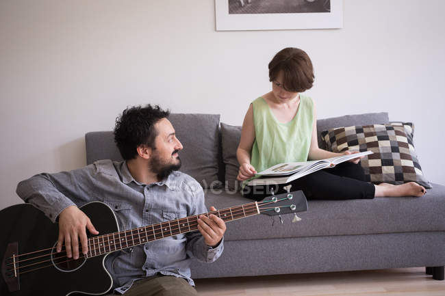 A young man is rehearsing on his bass guitar while his girlfriend is reading a book in the living room. — Stock Photo