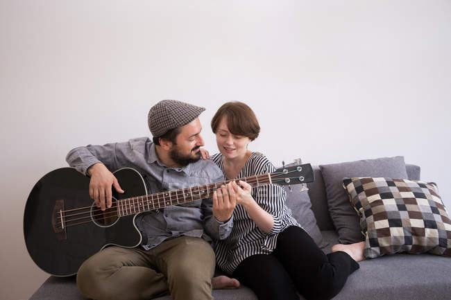 A young man is rehearsing on his bass guitar in the living room while his girlfriend admires him from the couch. — Stock Photo