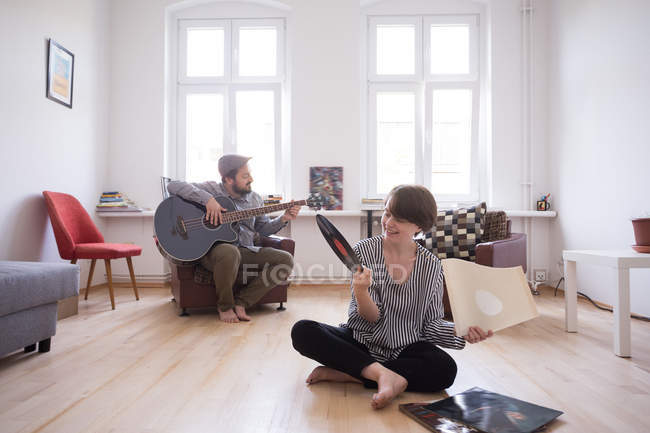 A young man is rehearsing on his bass guitar while the girlfiend is checking out vinyl records in the living room. — Stock Photo