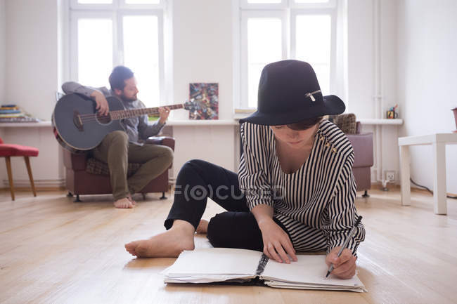 A young man is rehearsing on his bass guitar while the girlfriend is making drawings in the living room. — Stock Photo