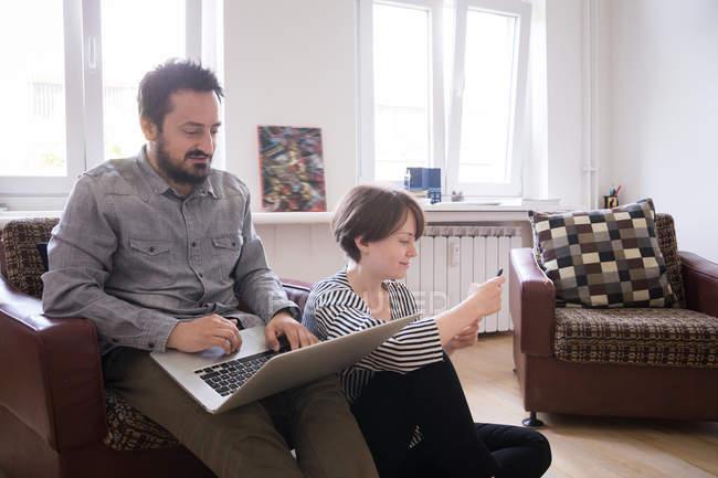 Um jovem casal está navegando na Internet e verificando o telefone inteligente enquanto relaxa na sala de estar . — Fotografia de Stock