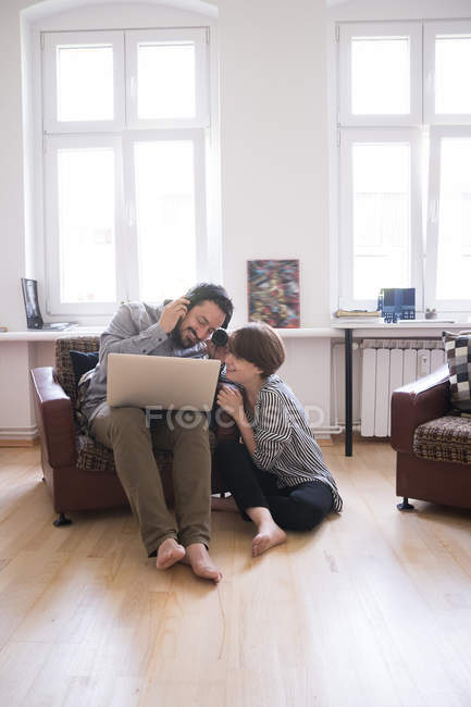 A young couple is listening to music from a computer in the living room. — Stock Photo