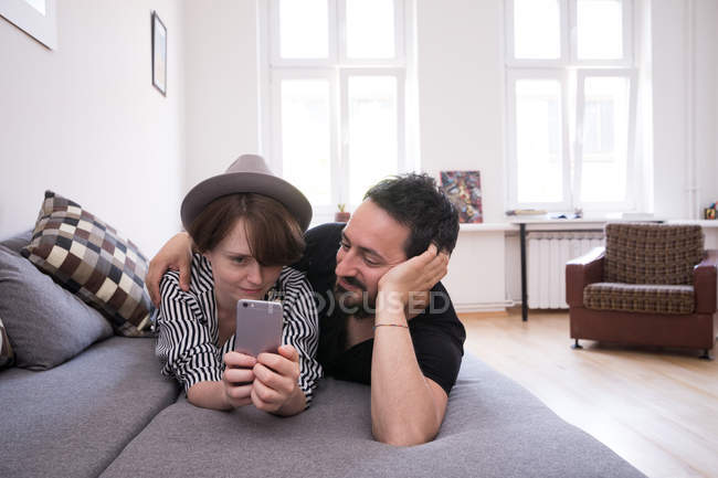 A young woman is checking her smart phone while her boyfriend is relaxing with her on the couch. — Stock Photo