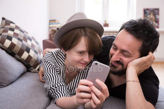 Um jovem casal está fazendo selfies com um telefone inteligente ao relaxar no sofá durante o fim de semana — Fotografia de Stock