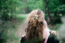 Rear cropped portrait of woman carrying blonde toddler girl in forest — Stock Photo