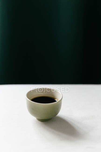 A coffee in a ceramic cup on a white surface against a dark background — Stock Photo