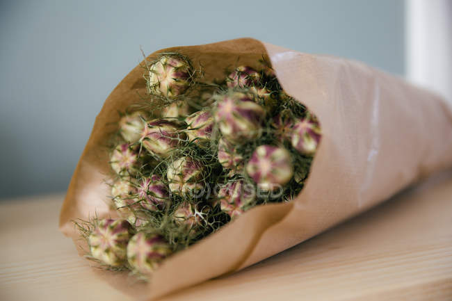 A Bouquet Of Dried Flowers Wrapped In Brown Paper Color Image