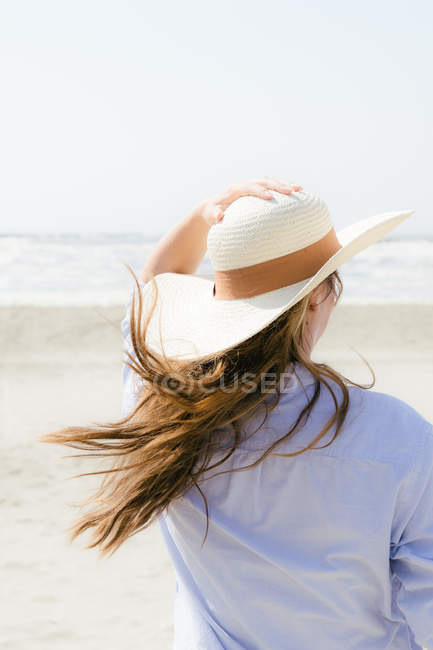Rear cropped portrait of woman on a beach holding sun hat — Stock Photo