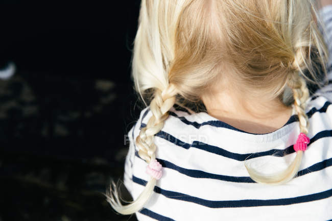 Cropped rear portrait of young blonde girl with two braids in white and blue striped shirt — Stock Photo
