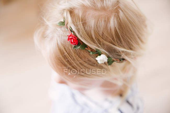 A blonde toddler girl wearing a flower head band with red and white roses — Stock Photo