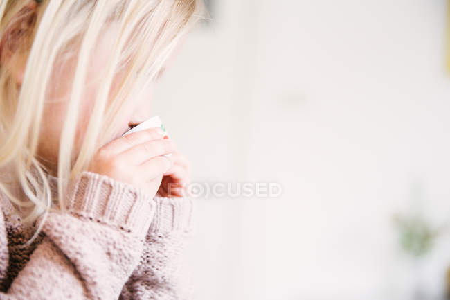 Cropped portrait of blonde toddler girl wearing light pink knitwear drinking tea — Stock Photo