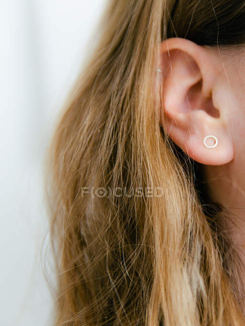 Partial view of woman face showing wearing earring shaped like circle — Stock Photo