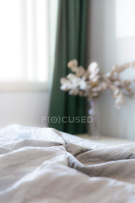 View from a grey and green toned bedroom with messy bed with in the background dark green curtains and a bouquet of eucalyptus — Stock Photo