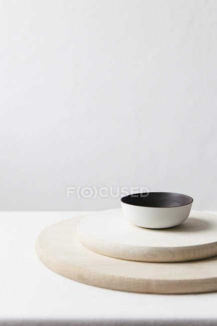 Una composizione di ceramica e piastre di legno su una superficie bianca — Foto stock
