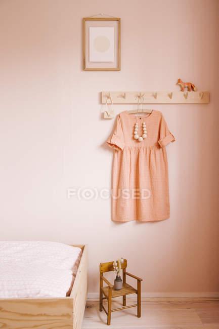 Девушки спальня сцена с coatrack, платье, кровать, кресло и крошечные искусство работы — стоковое фото