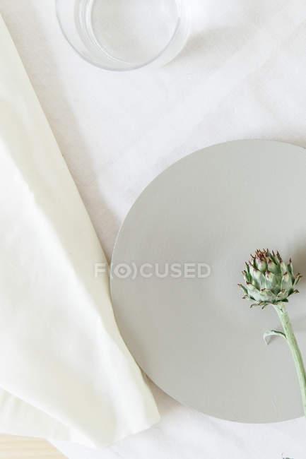 Fiore di carciofo piccolo sulla tabella bianca top grigio piatto e bicchiere d'acqua, visto dall'alto — Foto stock