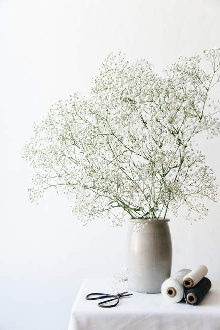 Bobbins of string and scissors on white table top with a bouquet of white baby breath, preparing to make floral wreath — Stock Photo