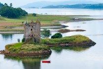 Reino Unido, Escocia, Argyll y Bute, Vista del Castillo Stalker en la pequeña isla rocosa de marea en el Lago Loch y barco rojo pasando por - foto de stock