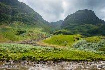 Великобритания, Шотландия, Хайленд, Ballachulish Glencoe зеленый пейзаж гор с небольшой ручей — стоковое фото