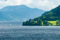 United Kingdom, Scotland, Highland, Inverness, Urquhart Castle, Loch Ness Castle by lake with sailing boat and mountains on background — Stock Photo