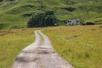 United Kingdom, Scotland, Highland, Ballachulish, way to the house at Glencoe place through green hills — Stock Photo