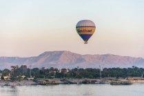 Globo volando sobre la costa del Nilo, Luxor, gobierno de Luxor, Egipto - foto de stock