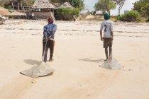 Tanzania, Zanzibar Città, Spiaggia, uomini che pescano piste — Foto stock