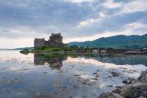 Reino Unido, Escocia, Highland, Dornie, Loch Duich, Eilean Donan Castle, Scottish Clan Clan Macrae, Eilean Donan Castle en un paisaje pintoresco con un lago que refleja el cielo - foto de stock