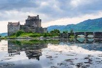 Reino Unido, Escocia, Highland, Dornie, Loch Duich, Eilean Donan Castillo con puente sobre el lago con reflejo del cielo - foto de stock