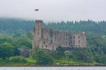 Великобритания, Шотландия, Хайленд, остров Скай, замок Данвеган в зелёных лесах на берегу озера — стоковое фото