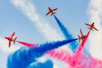 Regno Unito, Scozia, East Lothian, North Berwick, Red Arrows al Airshow annuale Scotlands nazionale in East Fortune, esecuzione di aerei nel cielo lasciando scie colorate, vista dal basso — Foto stock