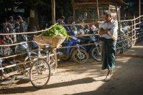 Bicicleta com cesta de legumes e homem passando perto de ciclomotores estacionamento no mercado de agricultores, Nyaung-U, região de Mandalay, Mianmar — Fotografia de Stock