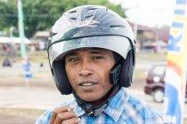 Asian man with helmet and cigarette in Jailolo, Kabupaten Halmahera Barat, Maluku Utara, Indonesia — Stock Photo