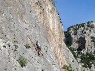 Sardegna, Italia - 20 ottobre 2013: Scalatore su una parete ripida scogliera di roccia — Foto stock