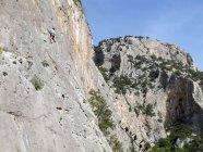 Sardaigne, Italie - 20 octobre 2013: Grimpeur sur une paroi rocheuse abrupte falaise — Photo de stock