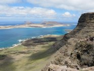 Spain, Canary Islands, Teguise, cliffs of the Famara massif and offshore island of La Graciosa with the town of Caleta del Sebo from above — Stock Photo
