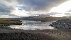 Vista panorámica de agua bahía y las montañas distantes, Islandia - foto de stock