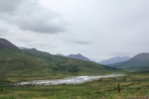 Canada, Yukon Territory, Yukon, On the Dampster Highway Judging North wilderness landscape with mountains and river under heavy sky — Stock Photo