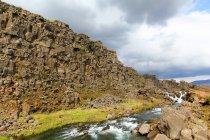 Rio rochoso por montanha sob céu nublado, Islândia — Fotografia de Stock
