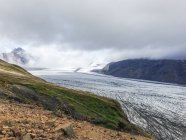 Glecier between mountains and low clouds, Iceland — Stock Photo