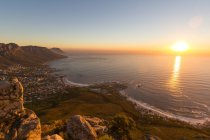 Sudáfrica, Cabo Occidental, Ciudad del Cabo vista aérea desde el Parque Nacional Table Mountain, paisaje urbano al atardecer junto a la costa del océano - foto de stock
