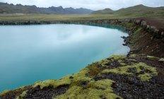 Лазурное озеро с скалистыми берегами на фоне горного хребта, Су-Урнес, Исландия — стоковое фото