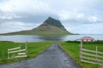 Сельский пейзаж с зеленым холмом в море, Исландия, Grundarfjorour — стоковое фото