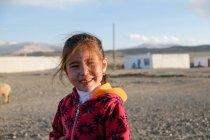 Asian girl smiling waving by hand at camera, Tajikistan — Stock Photo