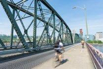 Люди ездят на велосипедах через мост Хоторн в Портленде, США — стоковое фото