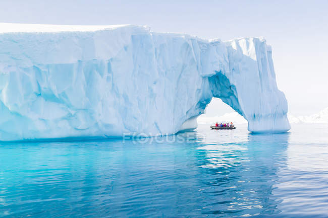 Nave da spedizione vista in un enorme iceberg in acqua blu, Antartide — Foto stock