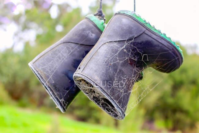 Gros plan de bottes en caoutchouc avec des toiles d'araignées — Photo de stock