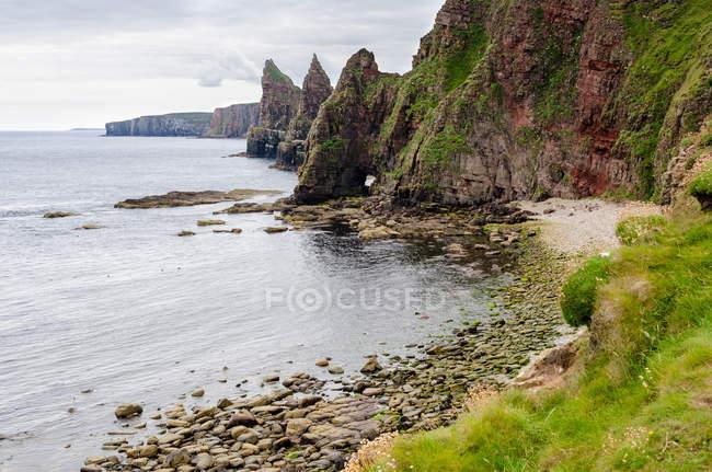 Vereinigtes Königreich, Schottland, Hochland, Docht, Steinstrand bei Duncansby Head mit Felsformationen und Felsspitzen — Stockfoto